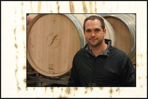 man next to wine barrel