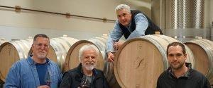 four men and wine barrels