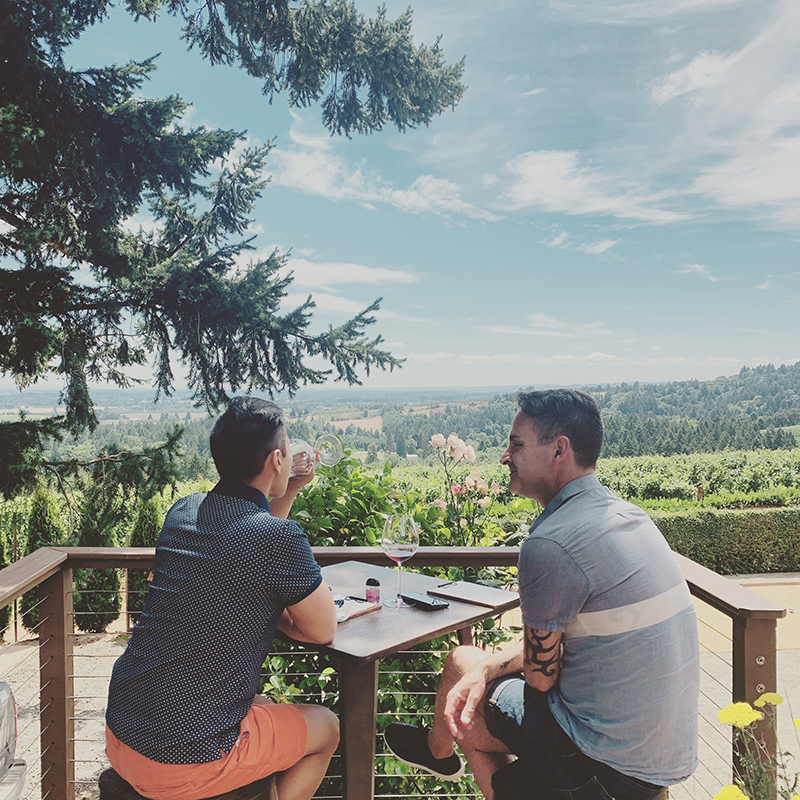 two men and a wine country view
